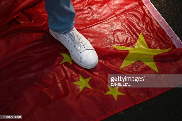 Foot is planted on a Chinese flag, laid on the ground during a vigil outside the Chinese Embassy in London on June 4, 2021 to mark the 32nd...