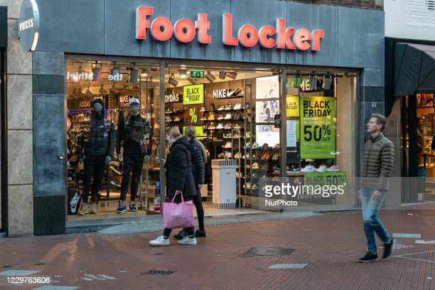 Foot Locker Store with people passing in front of it and a Black Friday sign with sale 50% as seen in the front display window of a shop in Eindhoven...