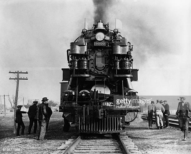 A 100 foot long threecylinder steam locomotive about to depart
