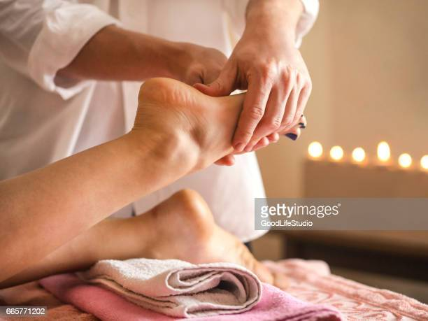 foot massage - woman lying on stomach with feet up stock photos and pictures