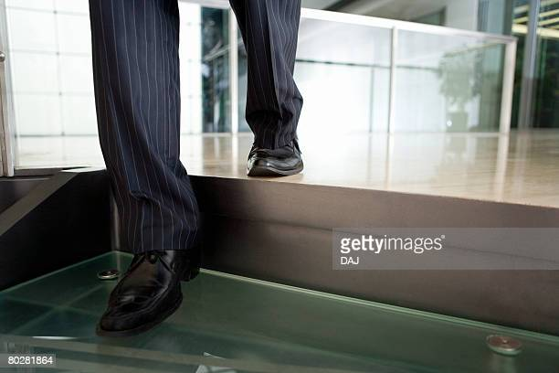 Foot of Businessman Taking Down Stairs, China, Beijing