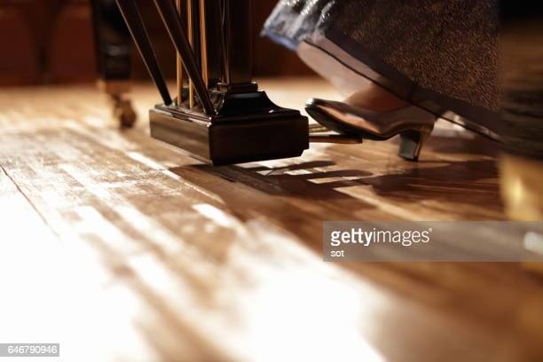 Foot of female pianist using piano pedal,close up