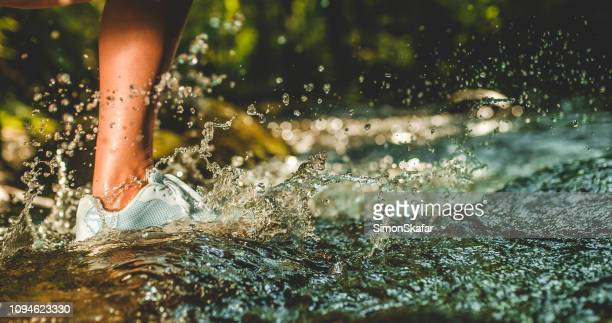 foot of person running through stream - river stock pictures, royalty-free photos & images