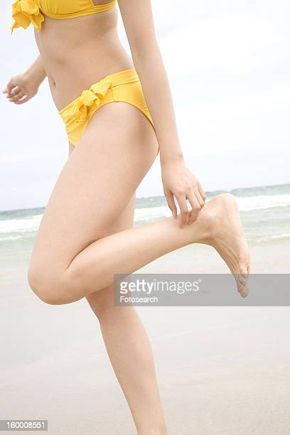 Foot of woman in swimsuit at the beach