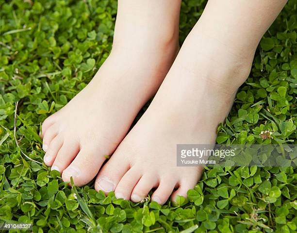 Foot of young girl on green grass