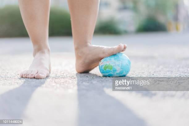 foot of young woman stepping on globe - zerstörung stock-fotos und bilder