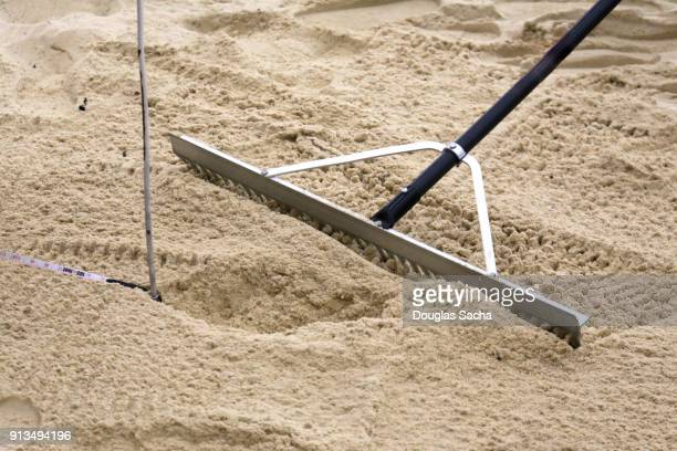 == Foot print in the sand gets measured after an long jumper athlete completes the track and field event  ==