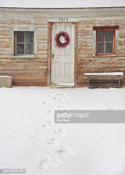 Foot prints leading to farm house with Christmas wreath on door