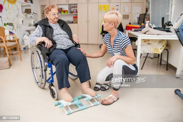 foot therapy in the nursing home for senior woman on wheelchair - blood flow stock pictures, royalty-free photos & images