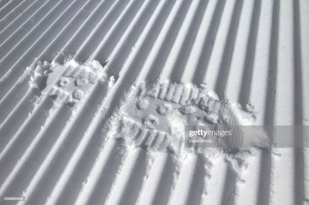 Foot track on the fresh striped prepared slope : Stock Photo
