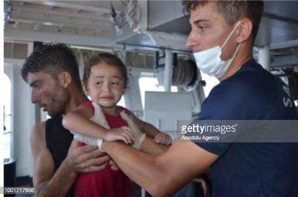 A footage captured shows that a migrant kid receives treatment as coast guard cutter carries out search and rescue work after a boat carrying...