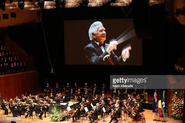 Footage of Bill Hawke conducting an orchestra is shown on a large screen during a state memorial service for the late former Australian prime...