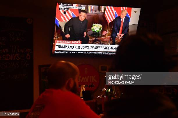 Footage of North Korea's leader Kim Jong Un meeting with US President Donald Trump during the USNorth Korea summit in Singapore is shown on a...
