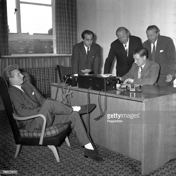 Football 15th July 1962 Manchester England Denis Law relaxes as he watches Manchester United Secretary Les Olive complete his new contract following...