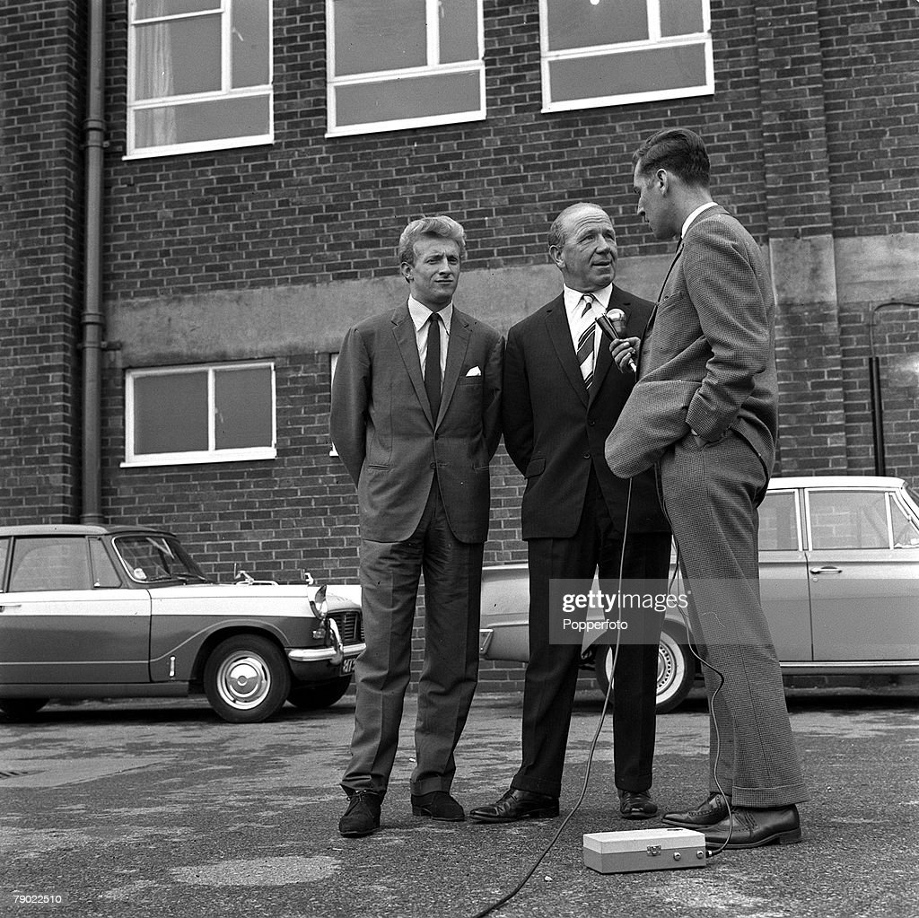 Football. 15th July 1962. Manchester, England. Manchester United Manager Matt Busby and new signing Denis Law are interviwed by a TV Reporter outside Old Trafford following Law+s complicated transfer from Italian club Torino. : News Photo