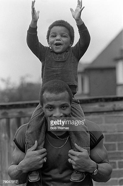 Football 18th October 1982 Portrait of West Bromwich Albion and England footballer Cyrille Regis playing with his son Robert in the garden of their...