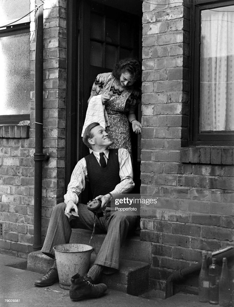 Football. 18th September 1946. Wallsend, Newcastle-upon-Tyne. Liverpool FC+s new ?12,500 signing (a then British record transfer fee) from Newcastle United Albert Stubbins, cleans the Bolton mud from his boots following his debut, as he talks to his wife. : News Photo
