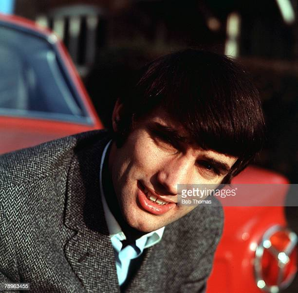 Football 1960's A picture of George Best the legendary Manchester United and Republic of Ireland footballer posing in front of his red sports car