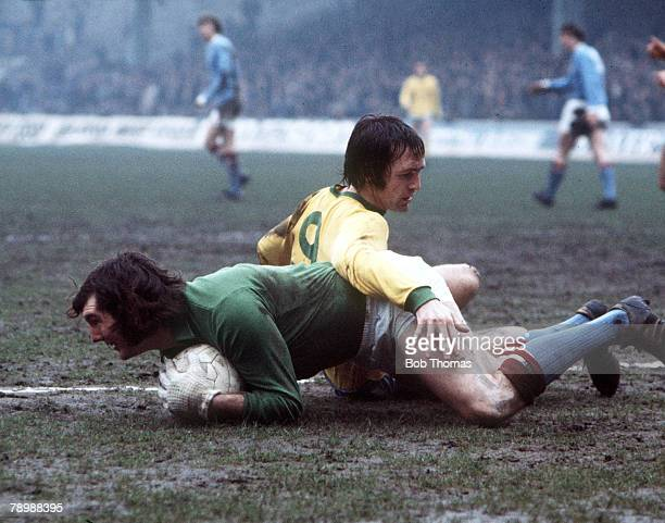 Football 1970's Manchester Citys goalkeeper Joe Corrigan safely gathers up the ball cloely challenged by West Bromwich Albion's Jeff Astle