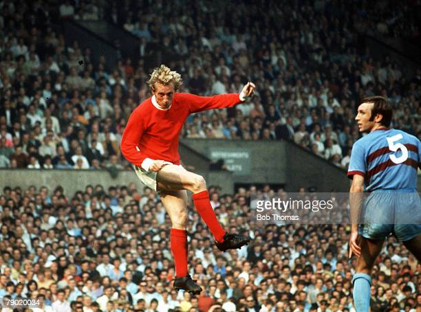 Football 1970's Manchester United's Denis Law jumps up for the ball during a league match with West Ham