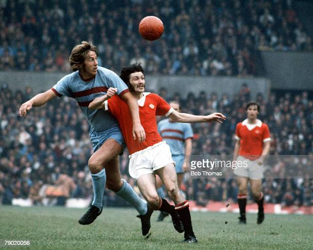 Football, 1970's, Manchester United+s Trevor Anderson jumps up for the ball in a challenge with a West Ham defender