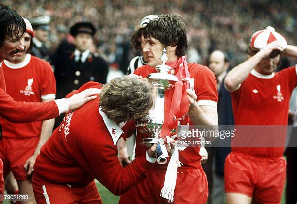 Football 1974 FA Cup Final Wembley Stadium 4th May Liverpool 3 v Newcastle United 0 Liverpools captain Emlyn Hughes holds the FA Cup as a fan who ran...