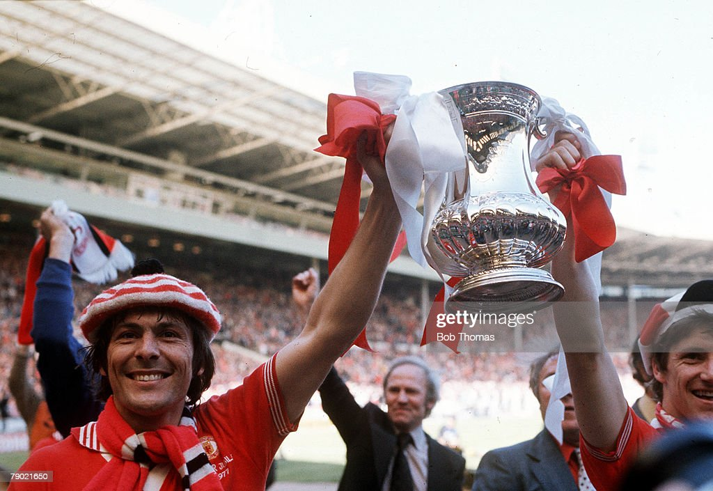 Football. 1977 FA Cup Final. Wembley. Manchester United 2 v Liverpool 1. 21st May, 1977. Manchester United goalscorer Stuart Pearson (left) and Gordon Hill proudly hold up the FA Cup trophy during celebrations after the match. : News Photo