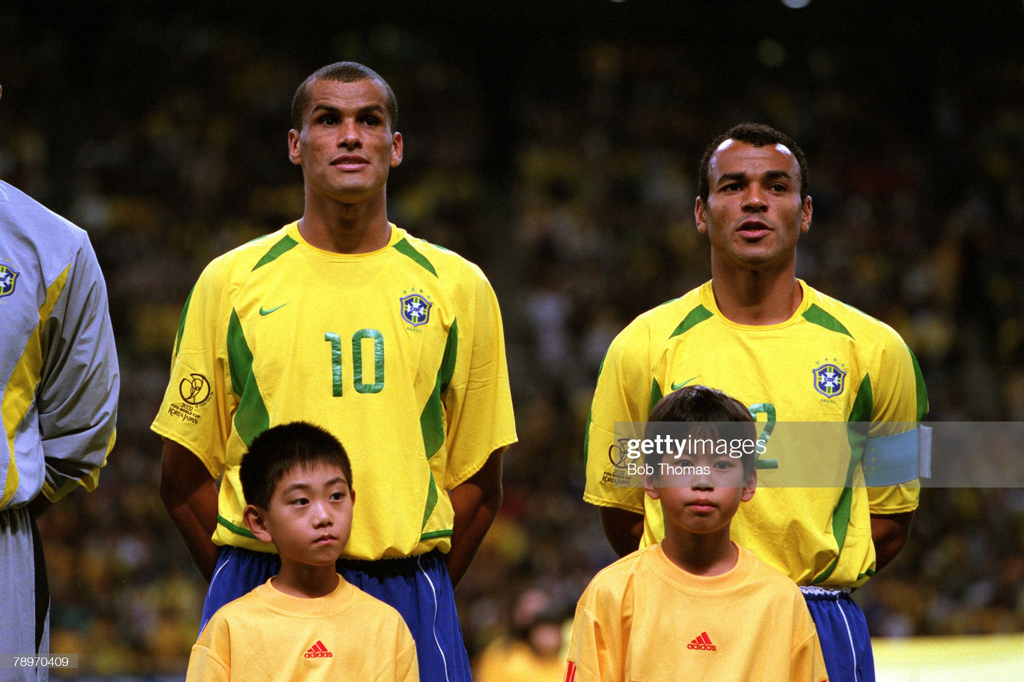 Football. 2002 FIFA World Cup Finals. Semi Final. Saitama, Japan. 26th June 2002. Brazil 1 v Turkey 0. Members of the Brazil team are pictured with mascots as they sing their anthem prior to the match. L-R: Rivaldo and Cafu (captain). Credit: POPPERFOTO/J : News Photo