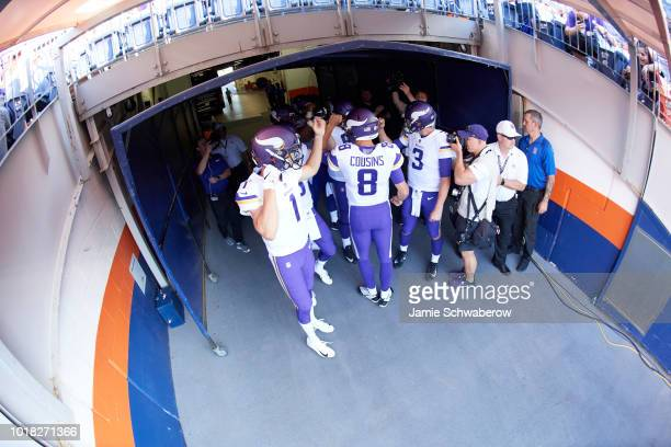Aerial rear view of Minnesota Vikings QB Kirk Cousins about to take field with teammates before preseason game vs Denver Broncos at Mile High Stadium...