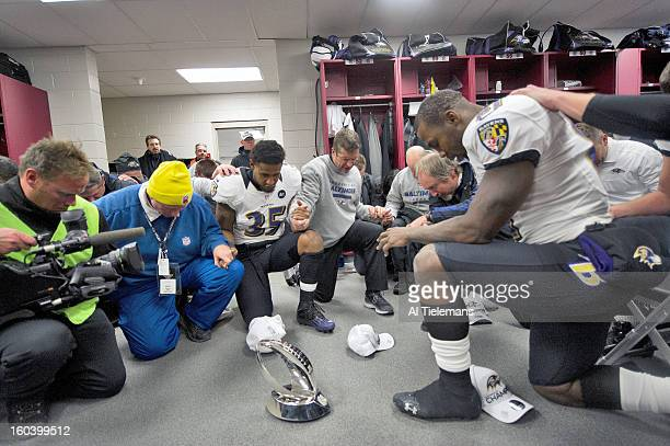AFC Championship Baltimore Ravens players say a prayer around the Lamar Hunt Trophy in the locker room after winning game vs New England Patriots at...