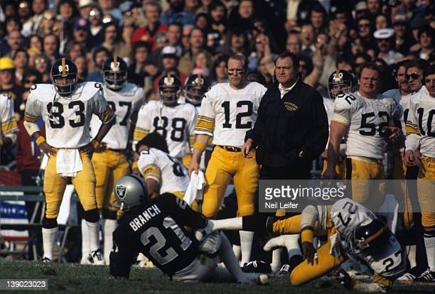 AFC Playoffs Pittsburgh Steelers head coach Chuck Noll on sidelines watching players Glen Edwards and Oakland Raiders Ciff Branch on ground during...