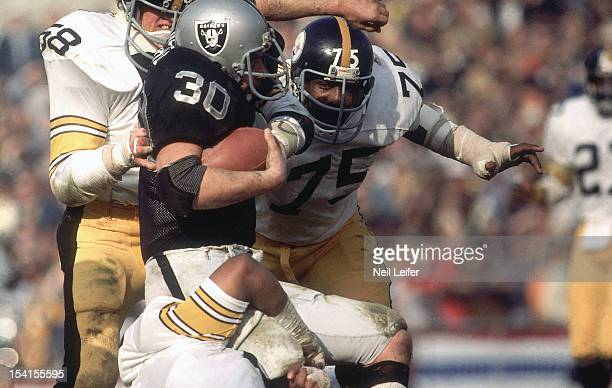 AFC Playoffs Pittsburgh Steelers Mean Joe Greene and Jack Lambert in action making tackle vs Oakland Raiders Mark van Eeghen at OaklandAlameda County...