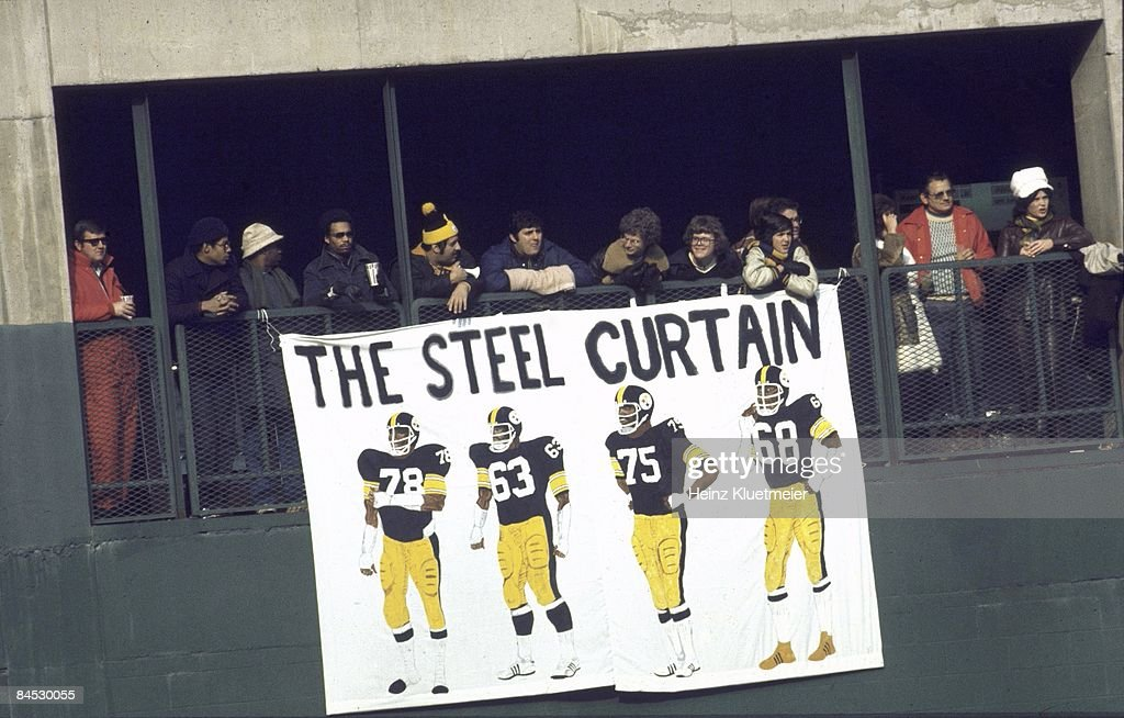 View of fans in stands holding Pittsburgh Steelers THE STEEL CURTAIN sign of defensive players (L-R) Dwight White (78), Ernie Homes (62), Joe Greene (75), and L.C. Greenwood (68) during game vs Buffalo Bills. Pittsburgh, PA