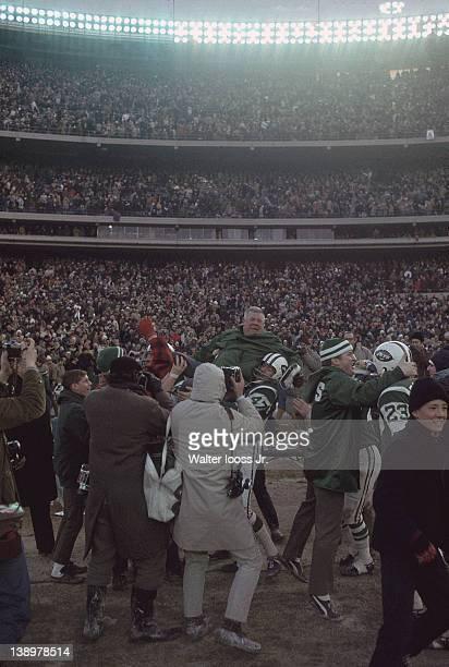 AFL Championship New York Jets players victorious hoisting head coach Weeb Ewbank after game vs Oakland Raiders at Shea Stadium Flushing neighborhood...