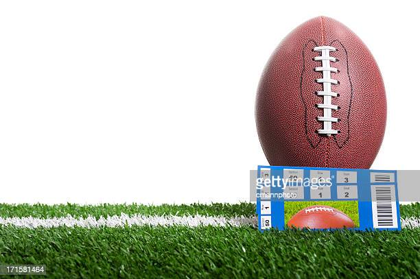 Football and game tickets on field with a white backdrop