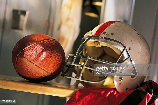 football and helmet with jersey on locker room bench - souvenir stock pictures, royalty-free photos & images