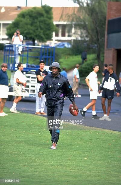 Atlanta Falcons Deion Sanders holding football while leaving practice for Atlanta Braves game from Falcons Facility Suwanee GA CREDIT Jim Gund
