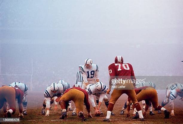 Football Baltimore Colts QB Johnny Unitas calling signals from line of scrimmage during game vs Washington Redskins at Memorial Stadium Fog weather...
