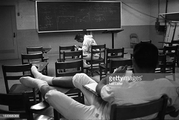 Baltimore Colts QB Johnny Unitas casual taking notes during meeting at Memorial Stadium Baltimore MD CREDIT Neil Leifer