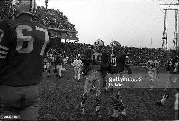 Baltimore Colts QB Johnny Unitas victorious shaking hands with San Francisco 49ers QB George Mira after winning game at Memorial Stadium Baltimore MD...