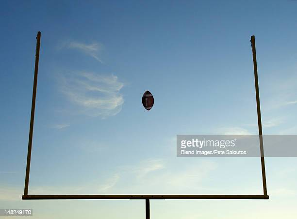 Football being thrown through goal posts