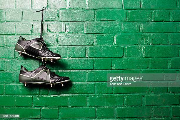 Football boots hanging in changing room wall far