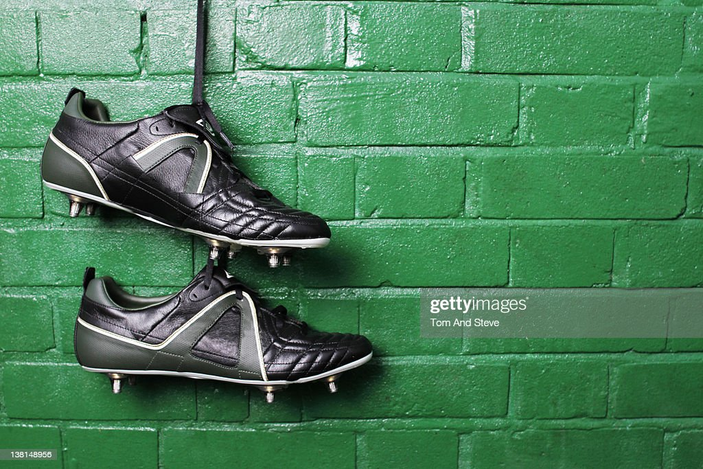 Football boots hanging in changing room wall. : Stock Photo