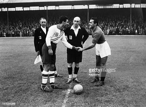 Football captains Maino Neri of Italy and John Souza of the USA shake hands before a first round match at Griffin Park Brentford during the London...