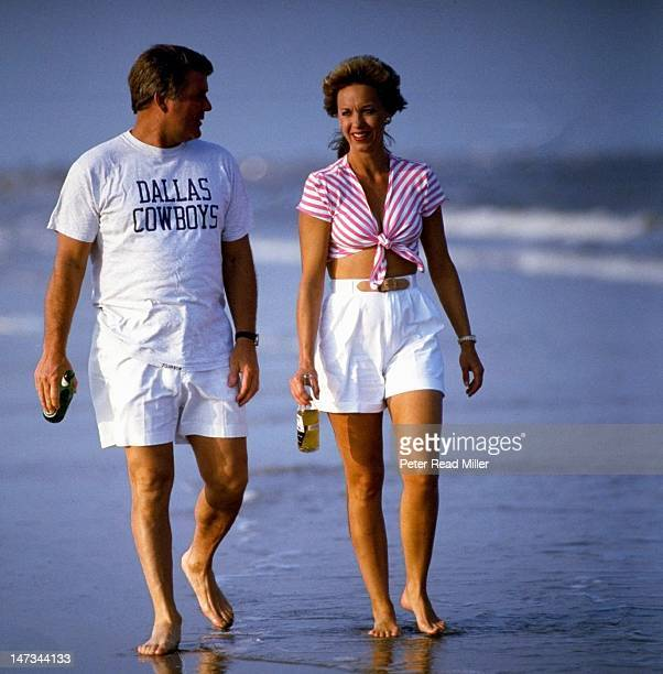 Casual portrait of Dalllas Cowboys head coach Jimmy Johnson and girlfriend Rhonda Rookmaaker walking on beach during photo shoot Crystal Beach TX...