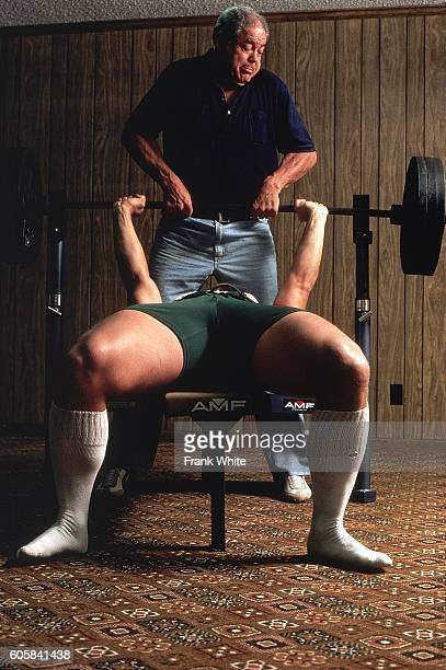 Casual portrait of New England Patriots offensive lineman John Hannah lifting weights on bench press with his father during photo shoot at home...