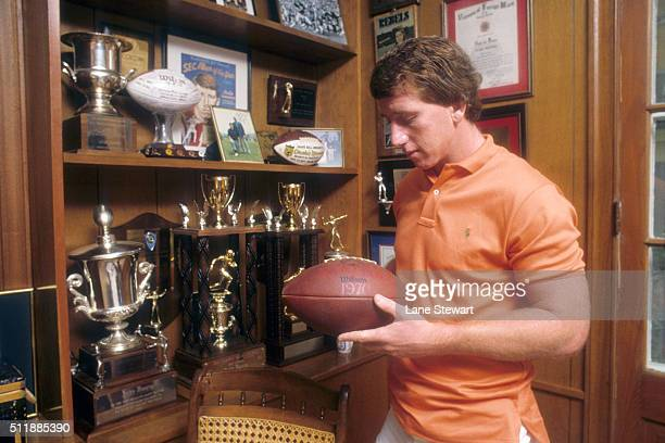 Casual portrait of New Orleans Saints QB Archie Manning holding Sugar Bowl ball from 1970 in trophy room during photo shoot at his Garden District...