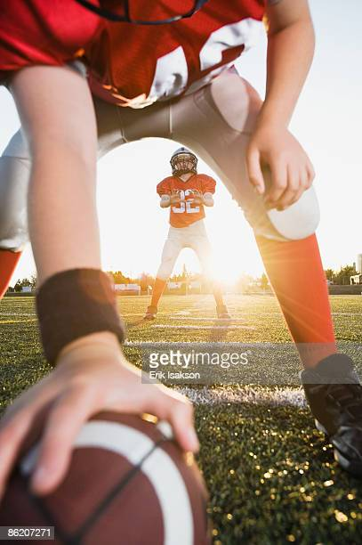 football center preparing to snap football to quarterback - snapping the ball stock pictures, royalty-free photos & images