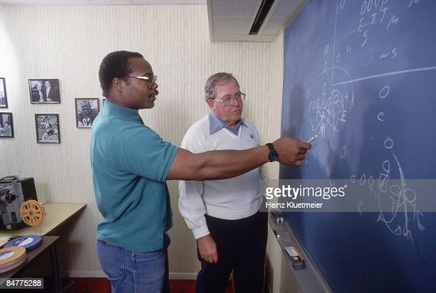 Chicago Bears defensive coordinator Buddy Ryan with Michael Singletary casual at blackboard before game vs Detroit Lions Chicago IL CREDIT Heinz...