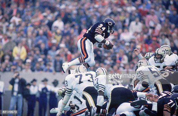 Chicago Bears Walter Payton in action, jumping over line of New Orleans Saints. Payton breaking rushing record of Jim Brown. Sequence. Chicago, IL...